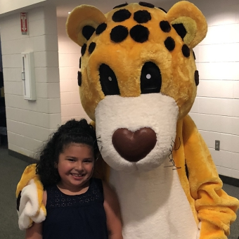 Cheetah mascot hugging child